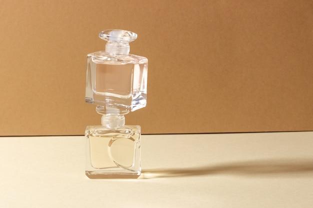 Frascos de perfume de vidro sob forte luz do sol com sombras fortes