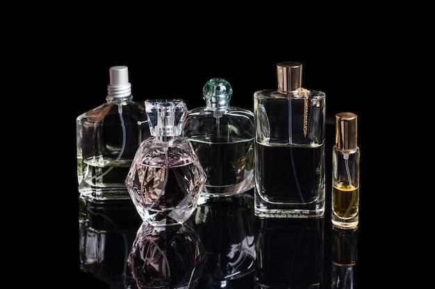 Frascos de perfume diferentes com reflexos na superfície preta
