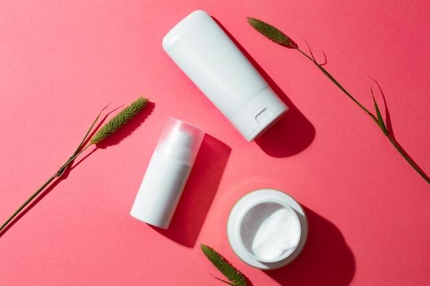 Frascos de produtos cosméticos brancos em branco em fundo rosa com espaço livre para texto como anúncio