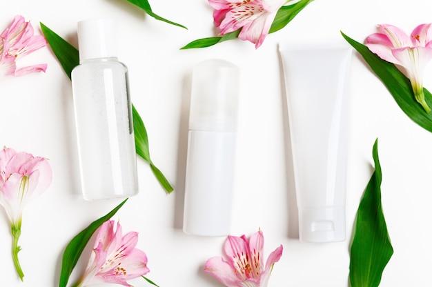 Frascos de produtos para a pele com flores de lírio. tubo de creme, distribuidor de corretivo, água micelar