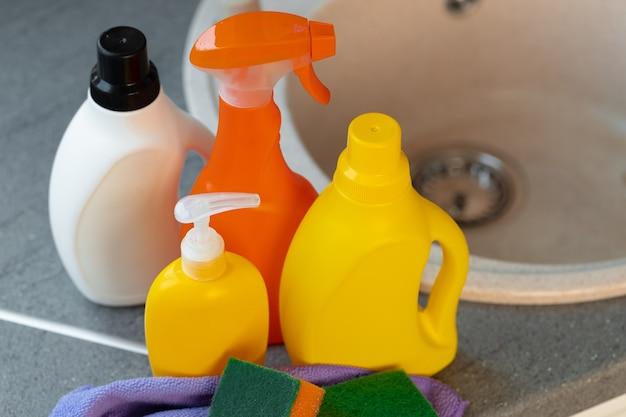 Frascos de produtos químicos domésticos perto da pia da cozinha
