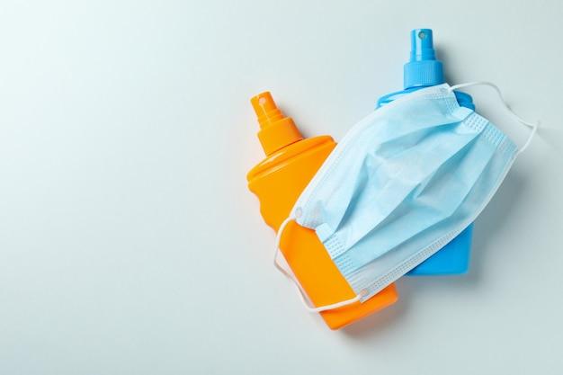 Frascos de protetor solar e máscara médica em fundo branco isolado