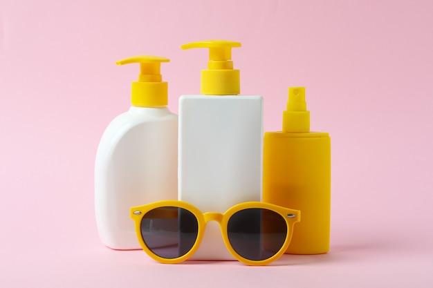 Frascos de protetor solar e óculos de sol em fundo rosa isolado