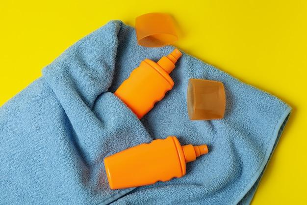 Frascos de protetor solar e toalhas em fundo amarelo isolado