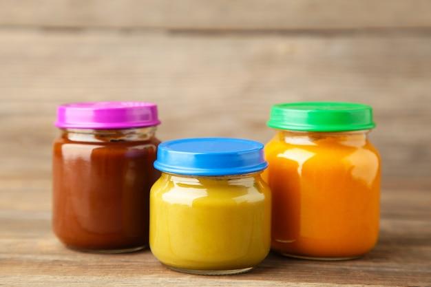 Frascos de purê de bebê na superfície cinza purê de frutas e vegetais
