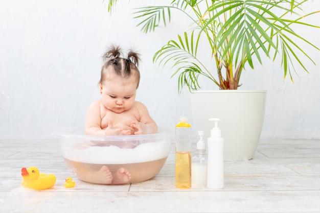 Frascos de shampoo em foco contra o bebê lavando em uma bacia com espuma