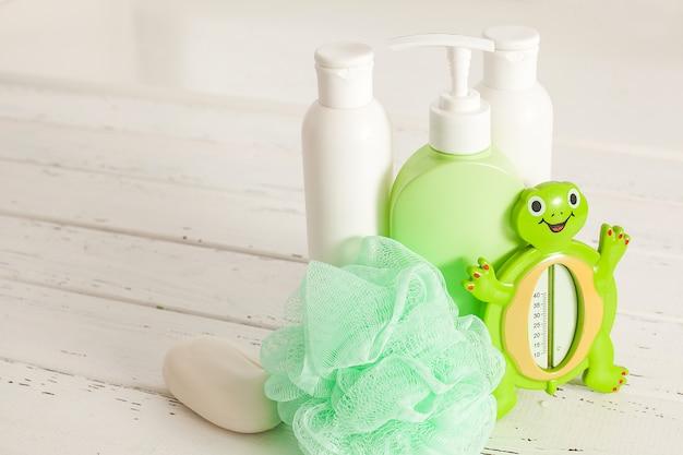 Frascos de shampoo na mesa de madeira. acessórios de banho para bebês. material de banheiro infantil. tubos de banheiro, bálsamo, sal marinho, sabão.