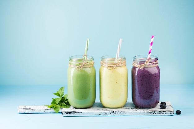 Frascos de smoothie colorido sobre fundo azul