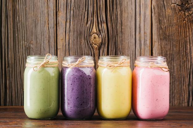 Frascos de smoothie colorido sobre fundo de madeira
