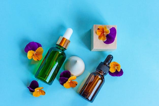 Frascos de soro de vidro com pipeta e lindas flores de viola sobre fundo azul. conceito de cosmético spa orgânico natural. vista do topo.