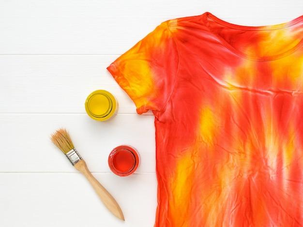 Frascos de tinta amarela e vermelha e uma camiseta tie dye na mesa