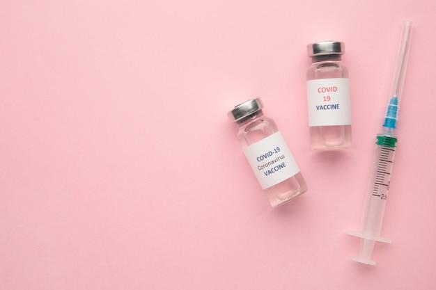 Frascos de vacina de coronavírus covid-19 e seringa em rosa com fundo de espaço de cópia. vista do topo