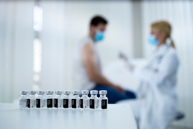 Frascos de vacinas na mesa e médico dando a vacina para homem jovem