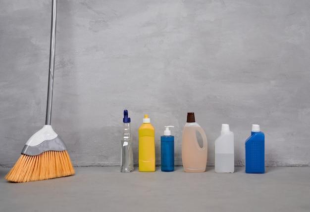 Frascos de vassouras de ferramentas e produtos de limpeza doméstica com diferentes detergentes no chão