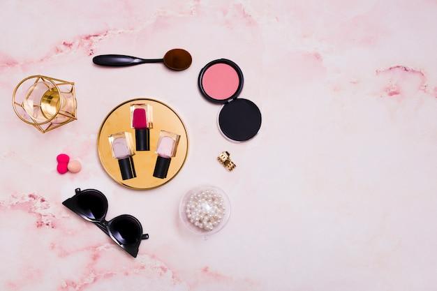 Frascos de verniz para unhas; colar; oculos escuros; esponja; pincel de maquiagem oval no fundo rosa