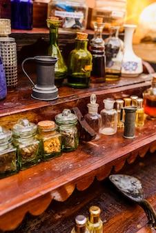 Frascos de vidro antigos com especiarias e perfumes em uma prateleira retro vintage.