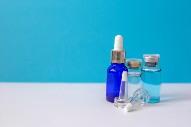 Frascos de vidro com ácido hialurônico ficam em azul
