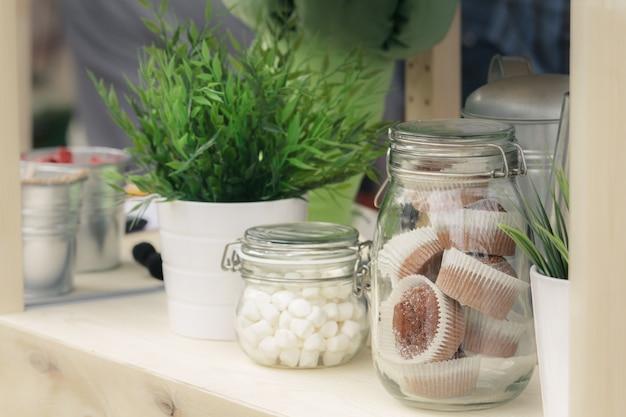 Frascos de vidro com biscoitos e muffins, mudas verdes em baldes decorativos de metal.