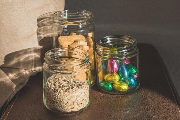 Frascos de vidro com bombons de chocolate, aveia, mel, biscoitos e chocolates