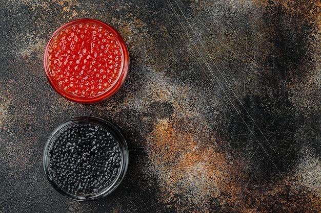Frascos de vidro com caviar preto e vermelho, na velha mesa rústica escura, vista de cima plana