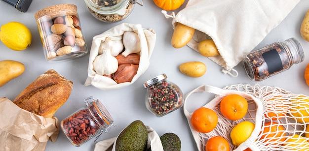 Frascos de vidro com grãos, sacolas reutilizáveis com legumes frescos, frutas