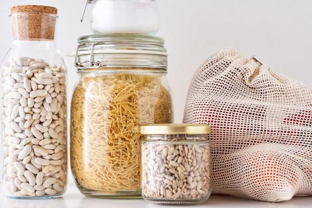 Frascos de vidro com ingredientes alimentares em um branco. zero conceito de desperdício. cozinha com utensílios ecológicos