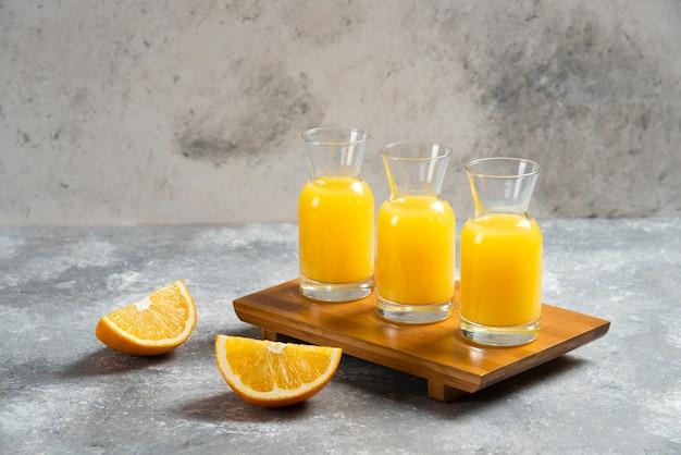 Frascos de vidro com suco de laranja e uma fatia de laranja.