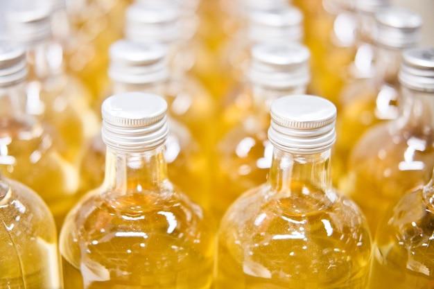 Frascos de vidro com suco de maçã amarela ou abacaxi. produção e recheio de bebidas