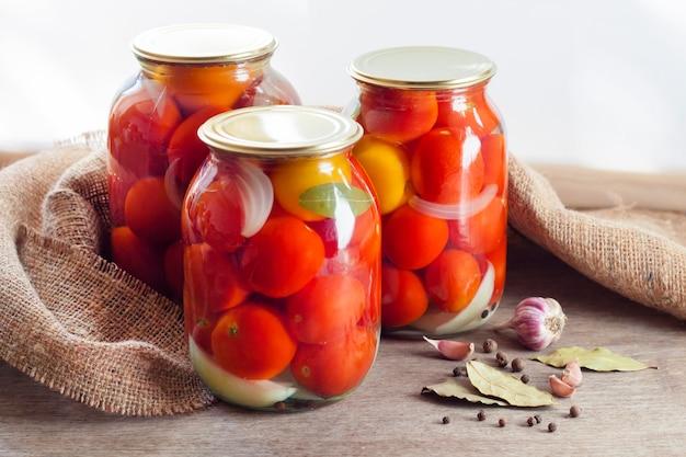 Frascos de vidro com tomates em conserva vermelhos, selados com tampa de metal