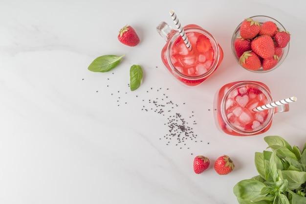 Frascos de vidro de bebida saborosa de morango com sementes de manjericão na mesa de mármore composição plana