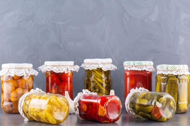 Frascos de vidro de pepinos em conserva e tomates na mesa de pedra.