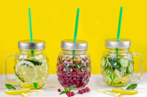 Frascos de vidro de verão fresco com água, limão, pepino, groselha e hortelã