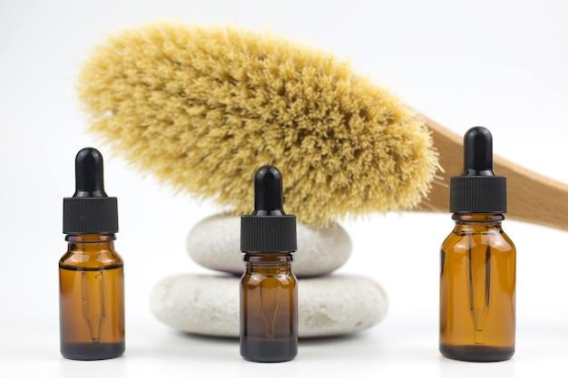 Frascos de vidro marrom com soro, produto essencial ou cosmético, escova de massagem seca