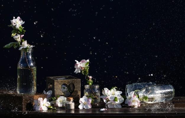 Frascos de vidro transparente e potes com água e flores de macieira em uma mesa de madeira rústica sob a queda de gotas de água. fundo escuro. copyspace