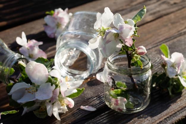 Frascos de vidro transparente e potes com água e flores de macieira em uma mesa de madeira rústica sob a queda de gotas de água. fundo escuro.