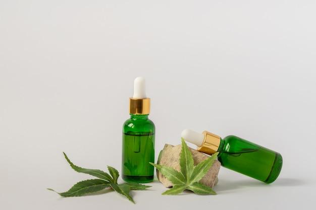 Frascos de vidro verde com óleo cbd, tintura de thc e folhas de cânhamo em uma superfície branca
