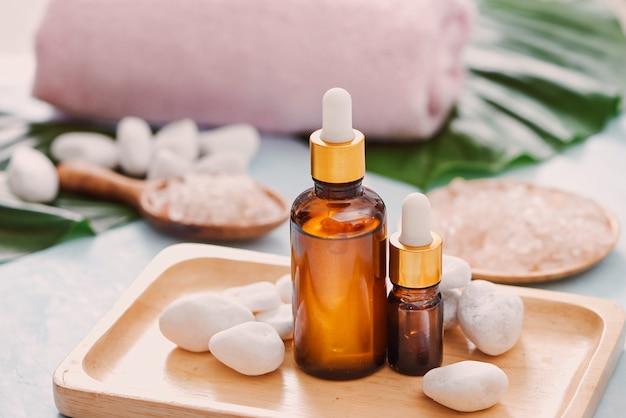 Frascos e conta-gotas. o produto de tratamento de beleza natural para a marca com o extrato de ingrediente orgânico, folha, óleo e vidro de laboratório