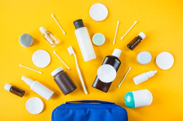 Frascos e recipientes com cosméticos e cotonetes com discos de um saco cosmético azul sobre um fundo amarelo.