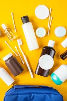 Frascos e recipientes com cosméticos e cotonetes com discos de um saco cosmético azul