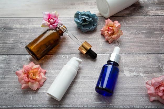 Frascos e uma pipeta com soro hialurônico para procedimentos cosméticos e cosméticos em um fundo de madeira com flores