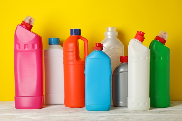 Frascos em branco com diferentes detergentes em fundo amarelo