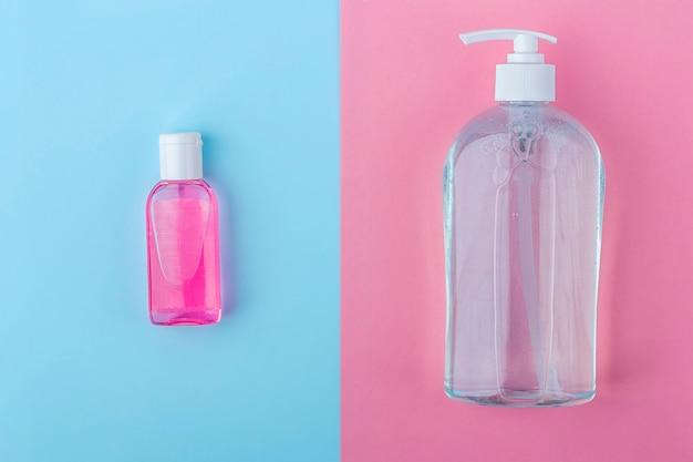 Frascos grandes e pequenos com gel desinfetante anti-séptico para lavar as mãos em fundo azul e rosa. gel de álcool como prevenção de coronavírus. conceito de prevenção de doenças virais.