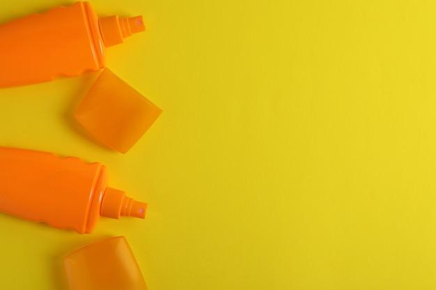 Frascos laranja de protetor solar em fundo amarelo isolado