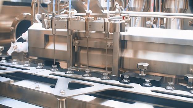 Frascos médicos em uma linha de produção automática para o preenchimento de vacinas e injeções. coronavírus
