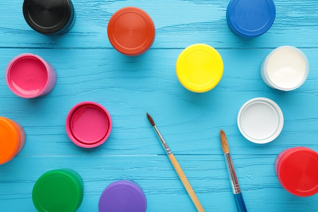 Frascos multicoloridos de guache e um pincel sobre um fundo azul. kit criativo.