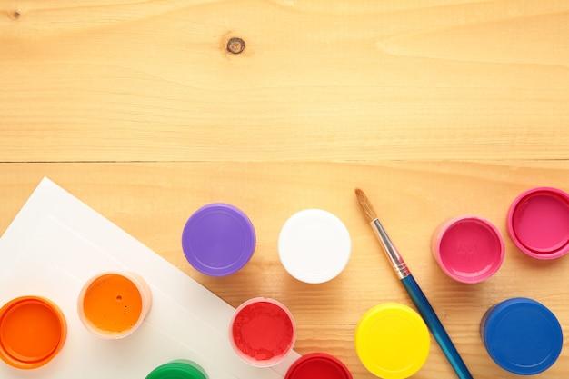 Frascos multicoloridos de guache e um pincel sobre um fundo claro. kit criativo.