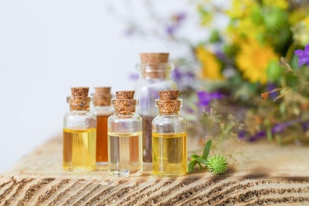 Frascos pequenos com óleos essenciais na mesa de madeira. conceito de medicina alternativa