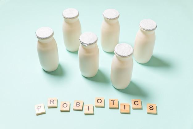 Frascos pequenos com probióticos e prebióticos bebem leite sobre fundo azul. produção com aditivos biologicamente ativos. fermentação e dieta alimentar saudável. bio iogurte com microorganismos úteis.