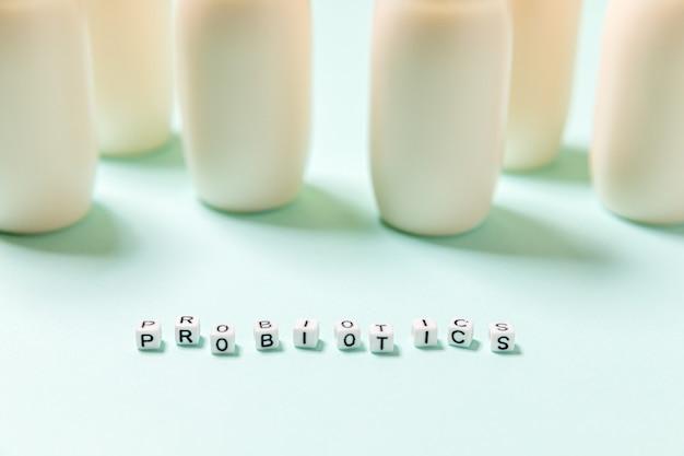 Frascos pequenos com probióticos e prebióticos bebida láctea em fundo azul