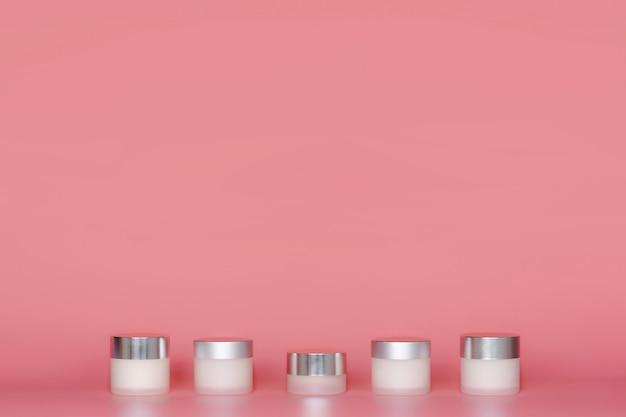 Frascos redondos do creme cosmético que estão no fundo cor-de-rosa.